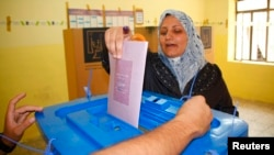 A woman casts her vote at a ballot box during the Iraq's provincial elections at a polling station in Mosul, 390 km (242 miles) north of Baghdad, June 20, 2013.