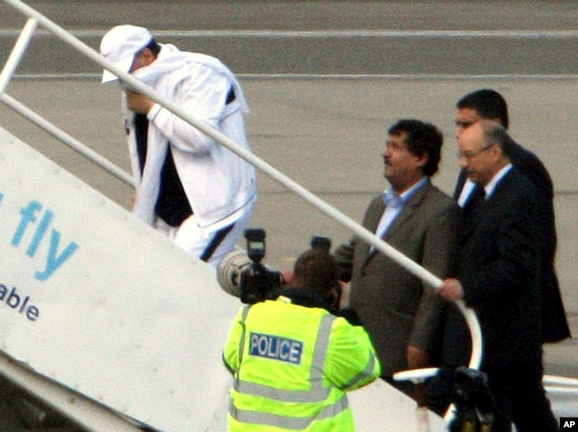 FILE - Lockerbie airline bomber Abdel Basset al-Megrahi, left, who was released from prison on compassionate grounds because he was terminally ill, boards an airplane accompanied by Libyan officials at Glasgow airport, Glasgow, Scotland, Aug. 20, 2009.