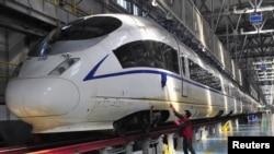 Seorang pekerja membersihkan kereta api berkecepatan tinggi Harmony CRH380B di Shenyang, propinsi Liaoning (23/12). Tiongkok mulai mengoperasikan rel kereta api kecepatan tinggi terpanjang di dunia, Rabu (26/12).