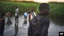 FILE - An unidentified man with a gun stands watch over displaced people, who have taken shelter from fighting, in a rebel-held part of Leer county, in Unity State, South Sudan.