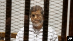 FILE - In this May 8, 2014 file photo, Mohammed Morsi sits in a defendant cage in the Police Academy courthouse in Cairo, Egypt.(AP Photo/Tarek el-Gabbas, File)