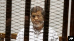 FILE - In this May 8, 2014 file photo, Egypt's ousted Islamist President Mohammed Morsi sits in a defendant cage in the Police Academy courthouse in Cairo, Egypt.(AP Photo/Tarek el-Gabbas, File)