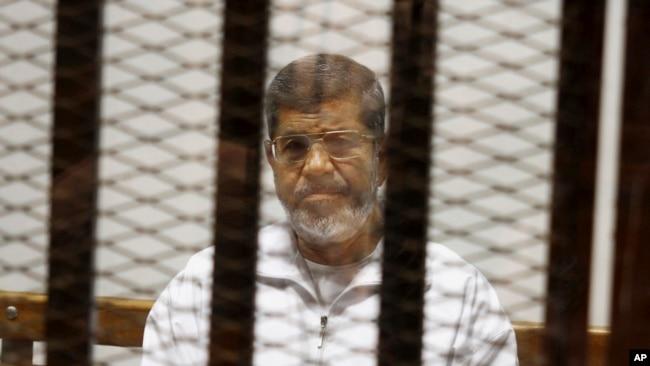 資料照:在位於開羅警官學院的法庭,被推翻的埃及總統穆爾西坐在囚籠內出庭。 (2018年5月8日)