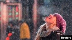 2014年1月2日游客在在纽约时代广场'品尝'雪花