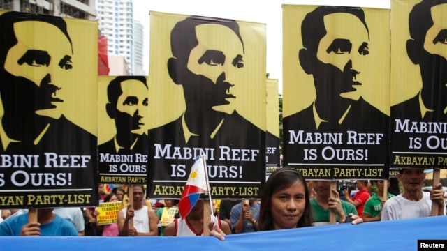 FILE - Protesters display placards with images of national revolutionary hero Apolinario Mabini as they march to the Chinese consulate office in Makati, Metro Manila, June 12, 2014.