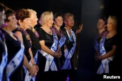 Contestants are reflected in a marble column during the annual Holocaust survivors' beauty pageant in the Israeli city of Haifa, Oct. 30, 2016.
