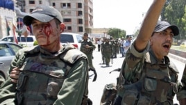 An injured Syrian army soldier (L) walks with his comrades after a roadside bomb hit their military truck, Daraa city, southern Syria, May 9, 2012.