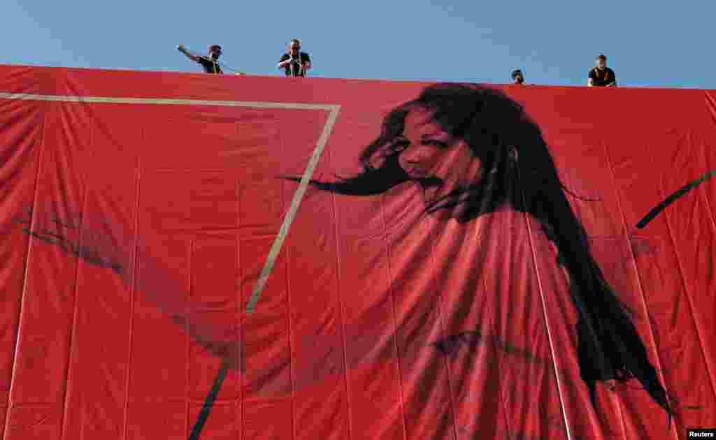 កម្មករកំពុងលើកផ្ទាំងបដារយក្សមួយនៃទិវាភាពយន្តលើកទី៧០ (Cannes Film Festival) ដែលមានរូបតារាសម្តែងស្រីអ្នកនាង Claudia Cardinale នៅក្នុងពិធីបុណ្យ Palais des Festivals ទីក្រុង Cannes ភាគអាគ្នេយ៍នៃប្រទេសបារាំងកាលពីថ្ងៃទី១៥ ឧសភា ២០១៧។