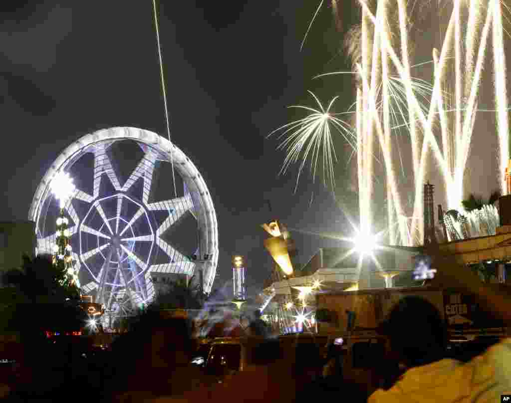 Fireworks light up the sky as onlookers welcome the new year, Manila, Philippines, Jan. 1, 2014.
