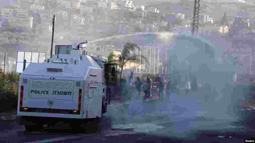 An Israeli police truck sprays water during during clashes between Arab youths and Israeli police at the entrance to the town of Kfar Kanna, in northern Israel, Nov. 8, 2014.