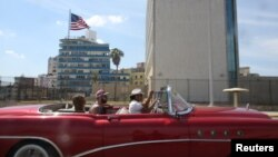 Tourists ride in a vintage car in front of the U.S. Embassy in Havana, Cuba, March 17, 2016.