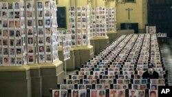 Seorang petugas keamanan duduk di antara potret orang yang meninggal akibat Covid-19, di Katedral, Lima, Peru, Sabtu, 13 Juni 2020. (Foto: AP)