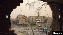 从叙利亚代尔祖尔被炸毁的房屋窟窿内可见人们在街上行走