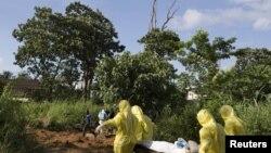 اعضای گروه دفن یک بیمار درگذشته از ابولا با لباس ایمنی مخصوص - فری تاون، سیرالئون، ششم مهرماه.