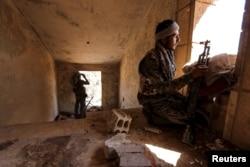 Tư liệu - Chiến binh YPG vào vị trí bên trong một tòa nhà bị hư hại ở khu al-Vilat al-Homor của thành phố Hasaka, Syria.