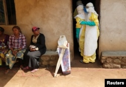 Health care workers enter a house where a baby suspected of dying of Ebola is, during the funeral in Beni, North Kivu Province of Democratic Republic of Congo, Dec. 18, 2018.