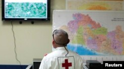 Anggota Palang Merah El Salvador mengamati berita gempa di San Salvador (13/10). (Reuters/Jose Cabezas)