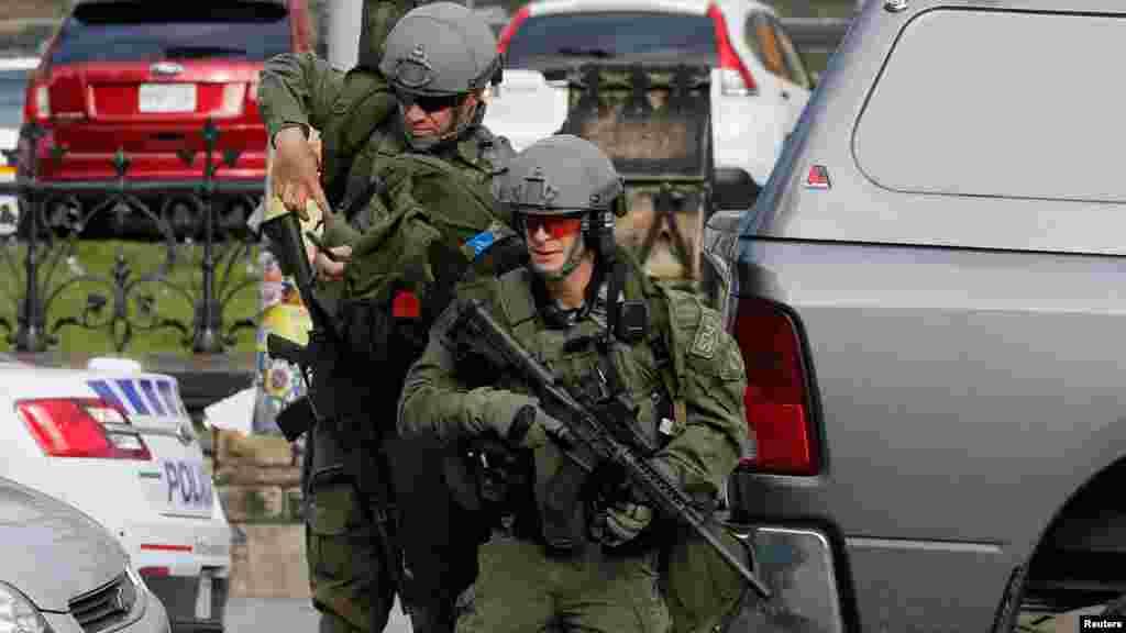 Des agents de la GRC, armés jusqu'aux dents, lancent un assaut à l'édifice du Parlement après une fusillade à Ottawa, le 22 Octobre 2014.