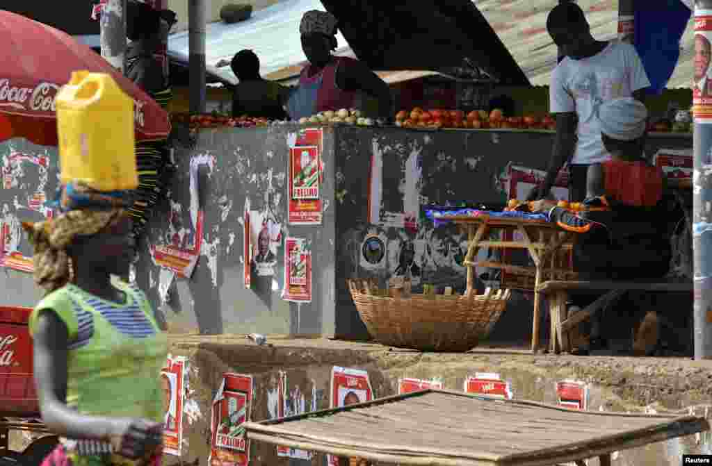 Electoral posters are pictured as vendors sell their wares at the central market in Gorongosa, central Mozambique, Nov. 19, 2013.