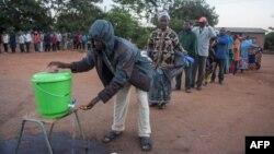 Des personnes font la queue pour se laver les mains afin de se protéger du coronavirus dans un bureau de vote, à Lilongwe, au Malawi, le 23 juin 2020.