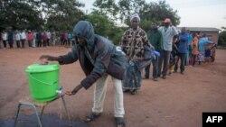 Warga Malawi antre untuk mencuci tangan dengan desinfektan di tengah pandemi Covid-19, sebelum memberikan suara di sebuah TPS di Lilongwe (foto: ilustrasi).