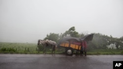 Orang-orang berlindung di bawah terpal plastik saat hujan deras setelah gunung berapi San Cristobal mengeluarkan asap dan abu, di dekat Chinandega, Nikaragua, Sabtu, 8 September 2012. (Foto: AP)