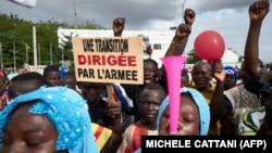Un homme tient une pancarte indiquant «Une transition menée par l'armée» alors que des partisans du CNSP (Comité National pour le Salut du Peuple) participent à un rassemblement sur la place de l'Indépendance à Bamako, le 8 septembre 2020.