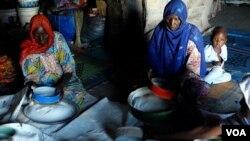 Women sift ground maize in a former warehouse where they live in Kawar Maila, a camp in Maiduguri, capital of northeastern Nigeria's Borno state. (Haruna Shehu/VOA)