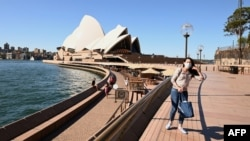 A lone tourist poses for a photo in Circular Quay in Sydney, Australia, March 20, 2020.