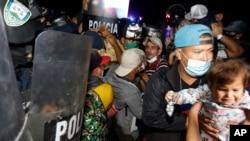 Las fuerzas de seguridad hondureñas tratan de evitar que los migrantes que intentan llegar a Estados Unidos crucen la frontera en El Florido, Honduras, hacia Guatemala, el viernes 15 de enero de 2021 a última hora.