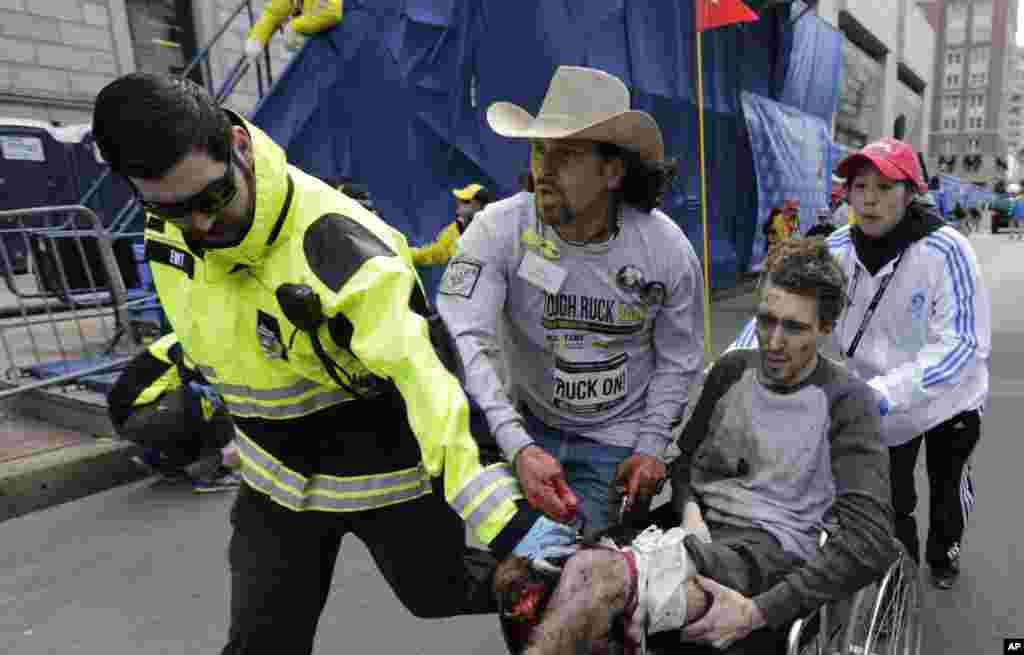 An emergency responder and volunteers, including Carlos Arredondo in the cowboy hat, push Jeff Bauman in a wheel chair after he was injured in an explosion near the finish line of the Boston Marathon April 15, 2013.