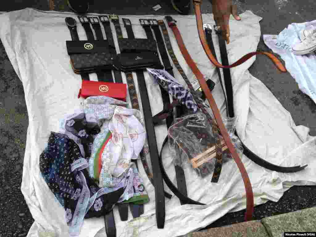 Des ceintures, des sacs à main et des foulards vendus par des migrants sénégalais dans les rues de Lima, Milan, 10 octobre 2015 (Nicolas Pinault/VOA)