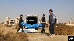 Suriyada yardım işçiləri Raqqa şəhərində kütləvi məzar yaxınlığında insan cəsədlərini daşıyır, 22 noyabr, 2018.