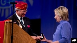 American Legion National Commander Dale Barnett presents an award to Democratic presidential candidate Hillary Clinton after she spoke at the American Legion's 98th Annual Convention at the Duke Energy Convention Center in Cincinnati, Ohio, Aug. 31, 2016.
