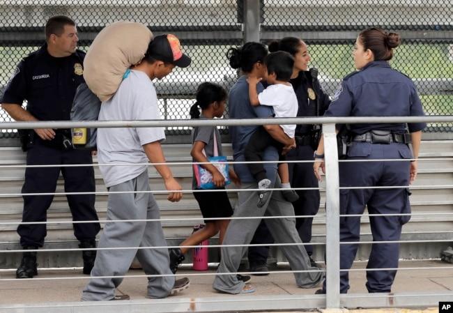 Ever Castillo, izquierda, y su familia, inmigrantes de Honduras, son escoltados al otro lado de la frontera por agentes de Control de Aduanas y Patrulla Fronteriza de EE.UU., el 21 de junio de 2018, en Hildalgo, Texas.