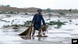 Một người đàn ông đi qua vùng đất lầy lội sau cơn lũ tại tỉnh Jawzjan, miền bắc Afghanistan, 25/4/2014