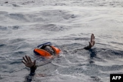 FILE - A migrant tries to board a boat of the German NGO Sea-Watch in the Mediterranean Sea, Nov. 6, 2017.