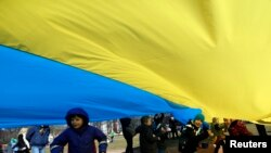 File - Children play as people hold up a giant Ukrainian flag to protest against the Russian intervention in Ukraine during the celebration of Lithuania's independence in Vilnius, Lithuania, Tuesday March 11, 2014.