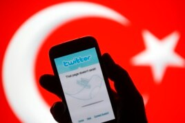FILE - A person holds a Samsung Galaxy S4 displaying a Twitter error message in front of Turkish national flag in this illustration taken in Zenica, March 21, 2014.