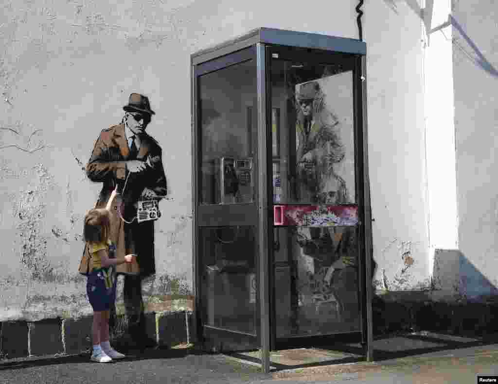 Bé Polly Dreezer, 3 tuổi, đứng cạnh bức tranh graffiti trên tường gần trụ sở của cơ quan nghe trộm của Anh ở Cheltenham, miền tây nước Anh.