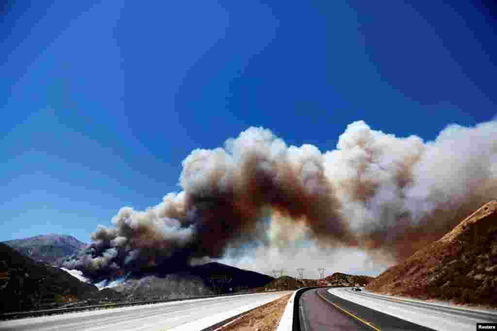ផ្សែងគ្របដណ្តប់ពីលើតំបន់ Interstate 15 អំឡុងពេលភ្លើងឆេះព្រៃ Blue Cut នៅ Cajon Pass ក្នុងក្រុង San Bernardino រដ្ឋ California។