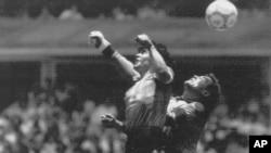 L'argentin Diego Maradona, à gauche, bat le gardien anglais Peter Shilton et inscrit son premier de deux buts en match de quart de finale de la Coupe du monde à Mexico ; un but controversé qualifié de la «Main de Dieu» et marqué du son poing gauche, à Mex