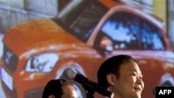 Li Shufu, Chủ tịch công ty xe hơi Geely của Trung Quốc (phải) nói chuyện tại một cuộc họp báo ở Bắc Kinh, phía sau là màn hình chiếu một chiếc xe Volvo