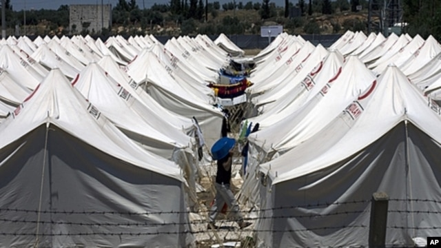 A Syrian refugee protects himself against the hot weather by wearing a plastic bowl on his head as he walks in a newly opened camp in Reyhanli, Turkey, June 24, 2011.
