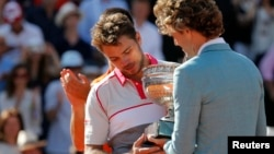 Former Brazilian tennis player Gustavo Kuerten (R) gives the trophy to Stan Wawrinka of Switzerland during the ceremony after he won the men's singles final match against Novak Djokovic of Serbia at the French Open tennis tournament, June 7, 2015.