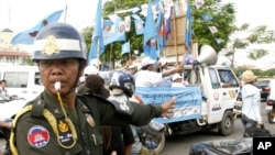 A Cambodian military police officer, left, traffics during the election campaign in Phnom Penh, file photo.