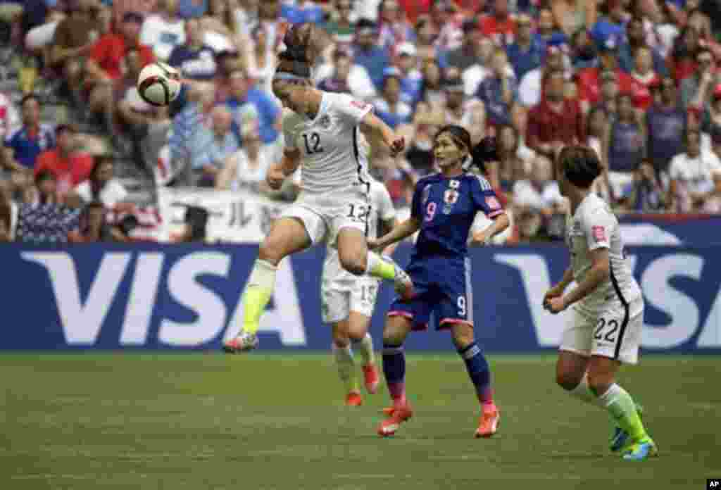 United States' Lauren Holiday (12) heads the ball above Japan's Nahomi Kawasumi (9) during the first half of the FIFA Women's World Cup soccer championship in Vancouver, British Columbia, July 5, 2015.