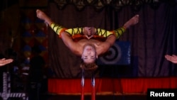A performer balances himself on a set of knives during a special preview as part of Christmas celebrations at the Ajanta circus in Kolkata, India, December 17, 2015.
