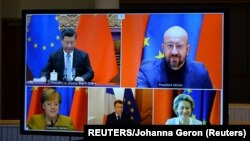 European Commission President Ursula von der Leyen, European Council President Charles Michel, German Chancellor Angela Merkel, French President Emmanuel Macron and Chinese President Xi Jinping are seen on a screen during a video conference, in Brussels, Belgium December 30, 2020