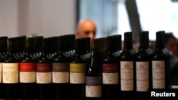 A man is seen behind bottles of wine inside a wine store in Buenos Aires, Argentina, Nov. 8, 2017.